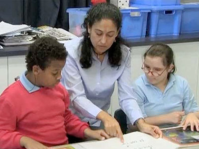 A Teacher helping two special needs students in class