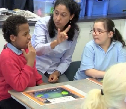 A teacher using sign language to communicate with her students